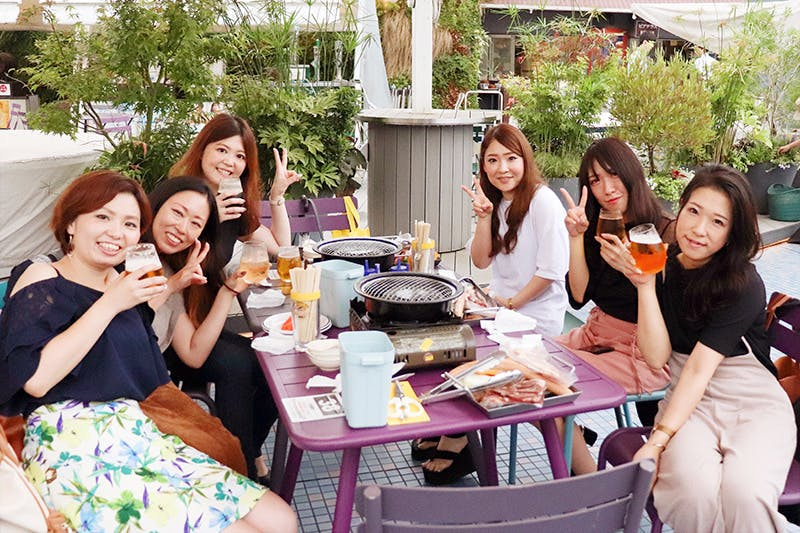 飲み物片手に笑顔でピースをする女性6人