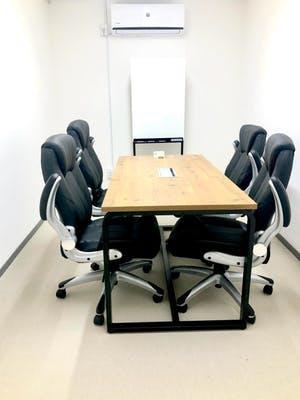 机と椅子とホワイトボードがあるオフィス